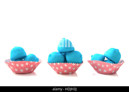 Blue marshmallows in pink white spotted cups isolated over white - Stock Photo