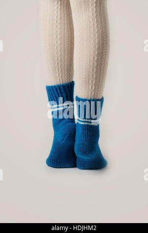 Female legs in white stockings and blue knitted socks. - Stock Photo