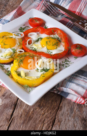 fried eggs with peppers and tomatoes on a plate close-up. vertical - Stock Photo