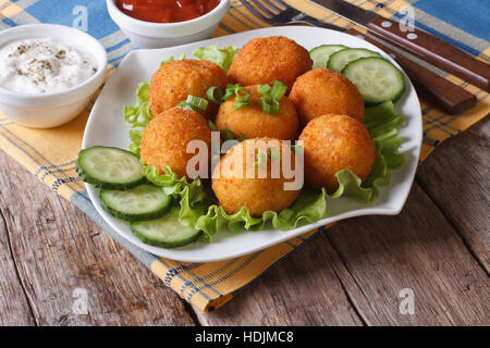 potato croquettes with lettuce and cucumber on a plate close-up. horizontal - Stock Photo
