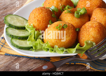Delicious potato croquettes and vegetables on a white plate close-up. horizontal - Stock Photo