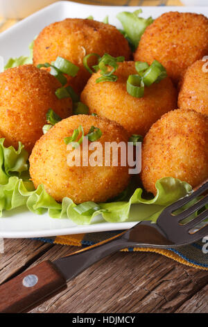 Delicious potato croquettes and vegetables on a white plate close-up. Vertical - Stock Photo