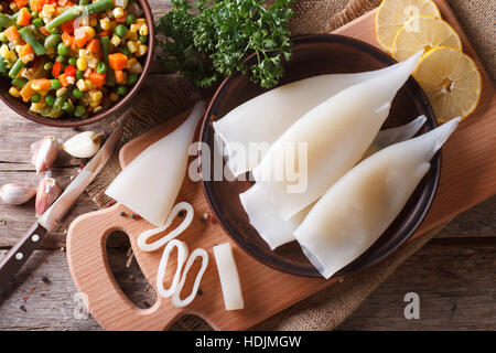 Preparation of raw squid and ingredients on the table. horizontal view from above - Stock Photo