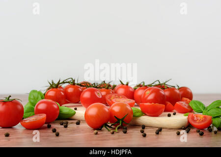Mini tomaotes on the wooden table with bright background. - Stock Photo