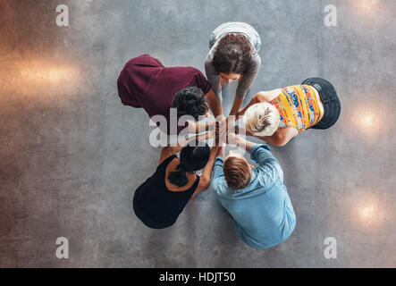 Top view of group of young people putting their hands together. Young students standing in a circle making stack - Stock Photo