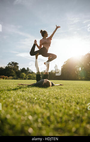 Vertical shot of healthy young couple doing acrobatic yoga on grass. Man and woman exercising in pair at the park. - Stock Photo