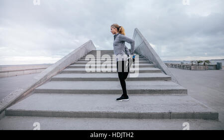 Side view of young female stretching her leg outdoors. Fitness woman preparing to run up the stairs during the workout. - Stock Photo