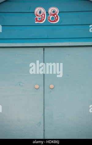 Close-up of number 98 in red on blue Beach hut above door - Stock Photo