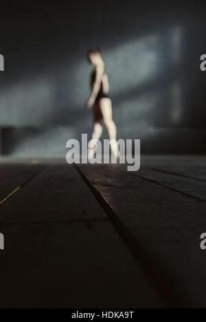 Slim ballet dancer standing on the tiptoes in the studio - Stock Photo