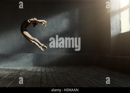 Professional ballet dancer performing in the dark lighted room - Stock Photo