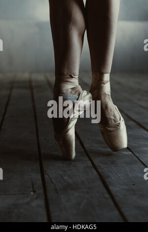 Ballet dancer standing on the tiptoes in the black room - Stock Photo