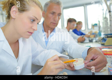 Supervisor guiding lady in manufacture of dentures - Stock Photo
