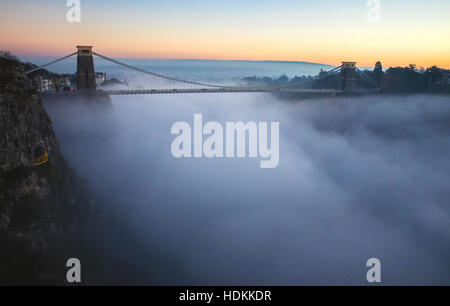 Clifton Suspension Bridge Bristol rising above inversion cloud in the Avon Gorge at dusk - Stock Photo