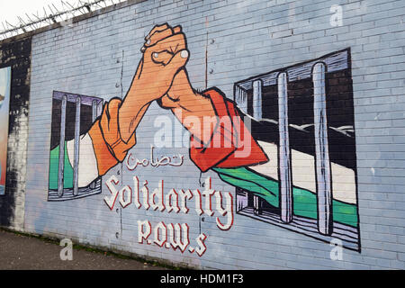 Belfast Falls Rd Rebublican Mural at Peace wall, Solidarity with POWs - Hands united between cells Ireland Palestine - Stock Photo