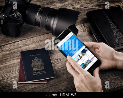 Woman hands with Apple iPhone 7 displaying flight information on a table with passports, a camera and a notebook, - Stock Photo