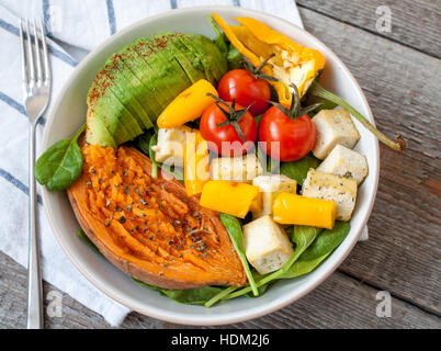 Salad with grilled vegetables: grilled sweet potatoes, tomatoes, avocados, spinach, tofu, pepper in a white bowl. - Stock Photo
