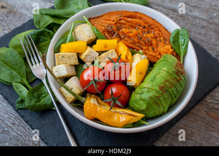 Salad with grilled vegetables: grilled sweet potatoes, tomatoes, avocados, spinach, tofu and pepper on dark slate - Stock Photo
