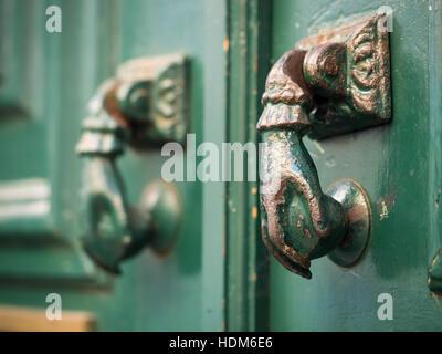 Old hand shaped metal door handles in Bairro Alto, Lisbon, Portugal - Stock Photo