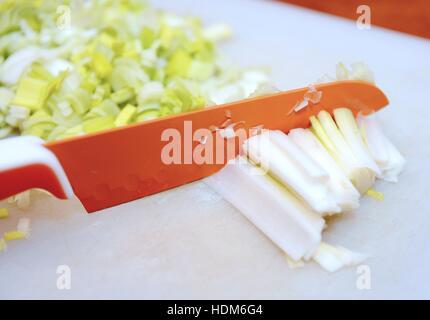 Closeup of knife cuts the fresh leek into small segments. - Stock Photo