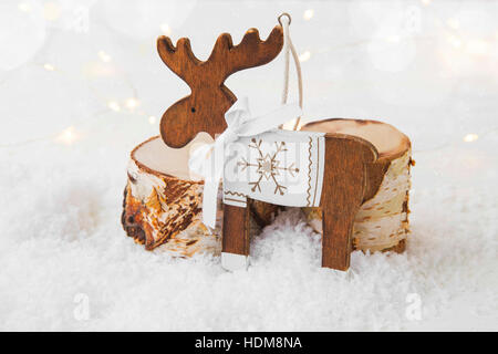 Wooden reindeer Christmas ornament on snow with background lights - Stock Photo