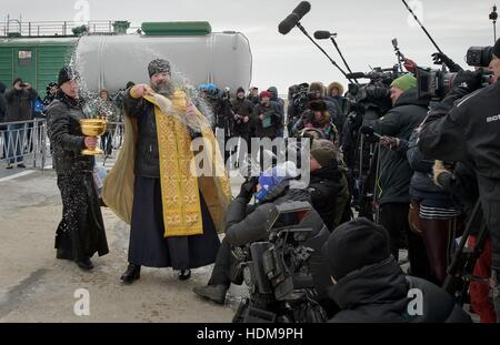 A Russian Orthodox Priest blesses members of the media after blessing the Soyuz MS-03 spacecraft rocket in preparation - Stock Photo