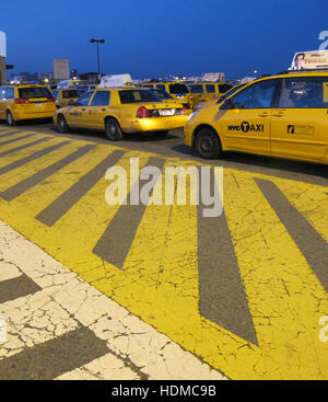 yellow cabs waiting in line at JFK' s Central Holding Lot waiting for their turn to go to terminals to pick up passengers - Stock Photo