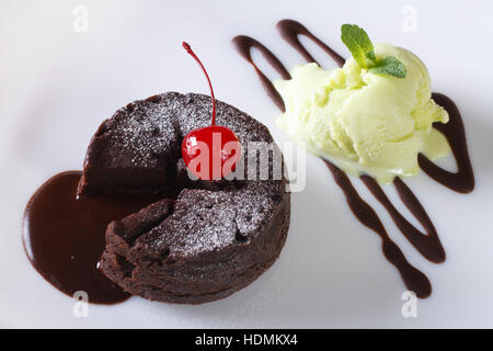 chocolate fondant cake with cherries and mint ice cream on a plate close-up. horizontal view from above - Stock Photo