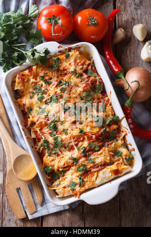 Mexican enchilada in a baking dish with the ingredients on the table. vertical view from above close-up - Stock Photo