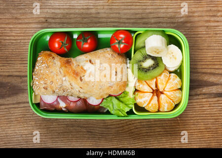 Lunchbox on wooden table. Ham sandwich and fruits in plastic box - Stock Photo