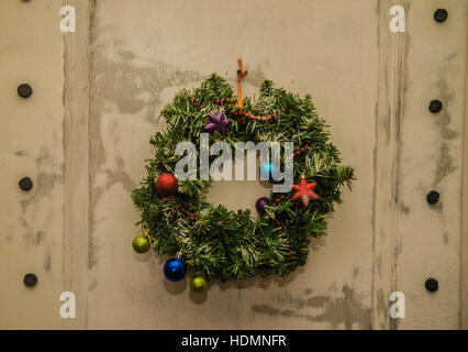 Christmas wreath on wooden door outdoor closeup. traditional green christmas wreath on wooden door. happy new year - Stock Photo