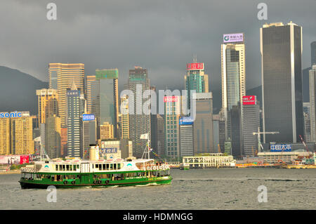 Star Ferry crossing Victoria Harbour between Kowloon and Hong Kong Island - Stock Photo