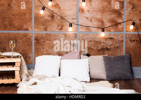 Glass of white wine in modern loft interior with light garland on wooden wall. - Stock Photo