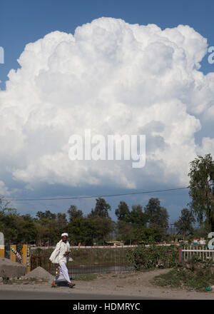 Indian man and big white cloud in the sky, India - Stock Photo