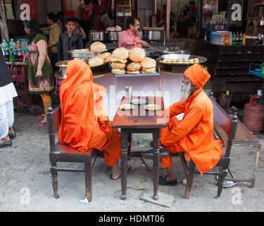 Two sadhus sitting outside a small restaurant in Haridwar, India - Stock Photo