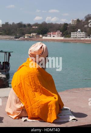 Holy man sitting on ferry pier waiting for boat,Rishikesh, India - Stock Photo