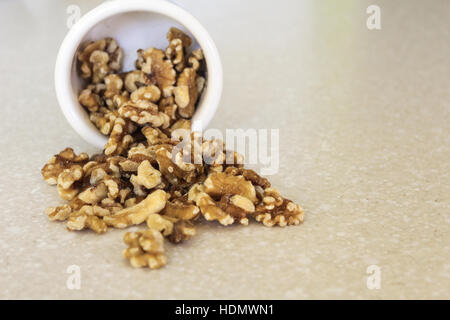 Delicious walnuts spilling out of a container on a kitchen countertop, ready to enjoy as a snack or in a favorite - Stock Photo
