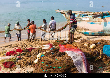 GALLE, SRI LANKA - DECEMBER 09, 2016 : Fishermen stood and work in the a boat on the beach at Galle city on December - Stock Photo