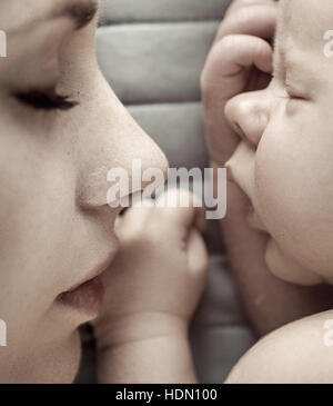 Cute sleeping newborn baby boy with his mother - Stock Photo