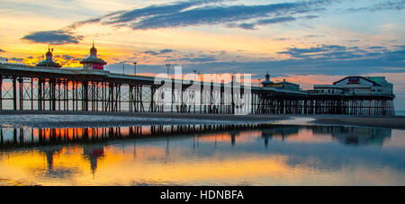 December Sunset with sea reflections, coloured evening hues as the sun sets over Blackpool, Victorian North Pier Lancashire: