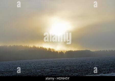 Sun shining through clouds and fog. Location: Aura, Finland - Stock Photo
