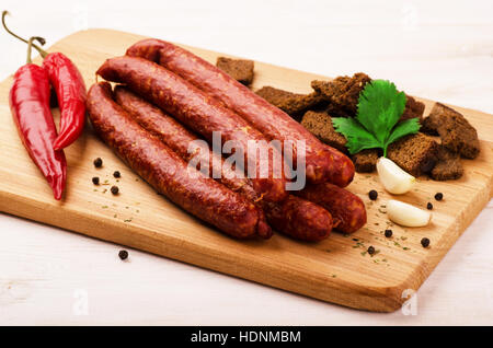 Smoked salami sausage with garlic, croutons and hot peppers on cutting board - Stock Photo