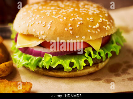 Fresh tasty burger and french fries on served paper close-up on restaurant table - Stock Photo
