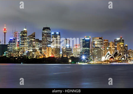 CLose up cityline of Sydney city CBD waterfront above harbour at sunset. Bright illumination of towers and landmarks.