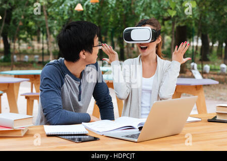 Happy young couple using virtual reality glasses and having fun at the table - Stock Photo