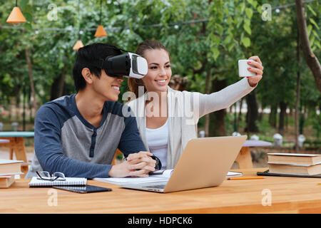 Smiling young couple using virtual reality glasses and taking selfie outdoors - Stock Photo
