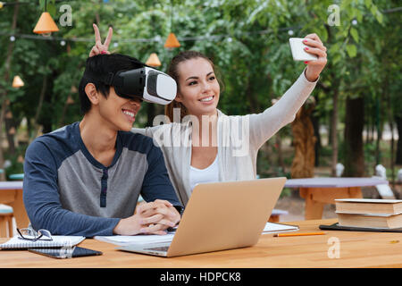 Cheerful young couple using virtual reality glasses and making selfie with smartphone outdoors - Stock Photo