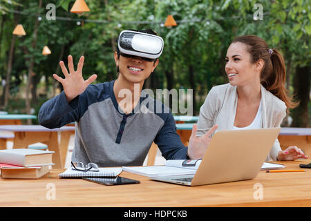 Smiling young couple using virtual reality glasses and laughing outdoors - Stock Photo