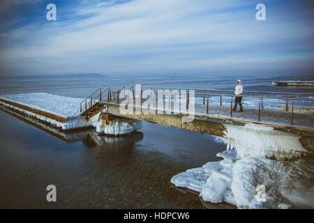 View of snow covered piers on frozen Blue sky - Stock Photo