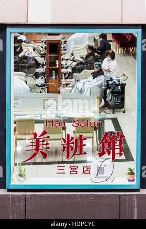 View through framed window of a Japanese ladies hair saloon with women sitting having their hair done Japanese kanji - Stock Photo