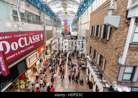 Japan, Kobe, Sannomiya. Overhead view of crowded shopping arcade. People walking through between two rows of stores - Stock Photo